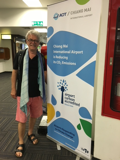 Prof. Thomas posing in front of an Airport Carbon Accreditation banner at Chiang Mai International Airport